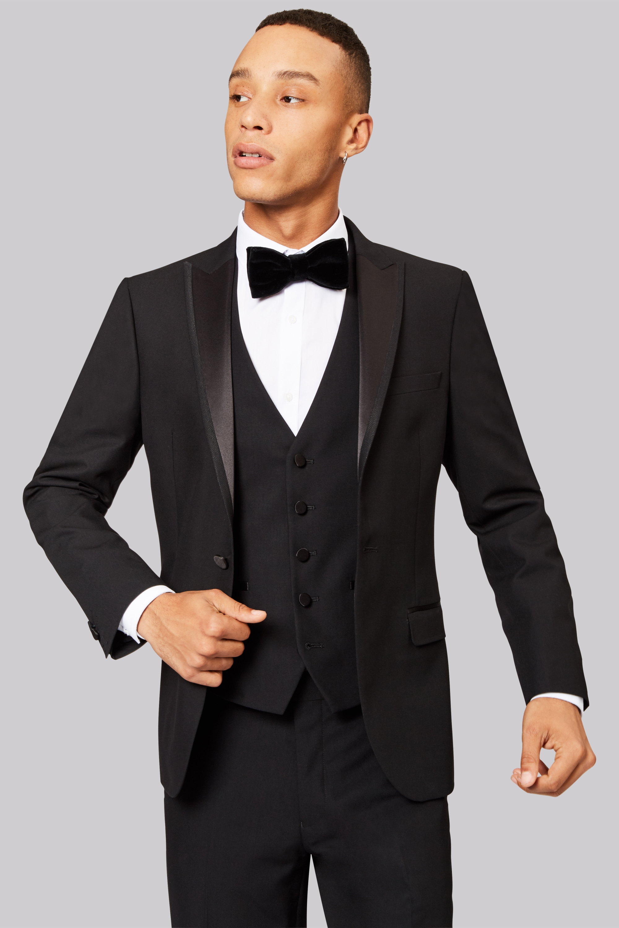A suit is a set of garments made from same cloth and consists of a jacket and trousers. A suit is ideal for formal occasions and is mostly worn at work during the day. A tuxedo (or tux) is a form of dinner jacket, different from a formal suit and more appropriate for semi-formal evening events or black tie events.